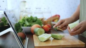 4K 切黄瓜果皮的女性手,成份为烹调做准备通过片剂跟随烹调在网站上的网上录象剪辑 股票视频