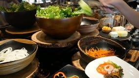 4K 在承办酒席自助餐食物的妇女精选的另外菜在旅馆餐馆用五颜六色的水果和蔬菜沙拉的 股票录像