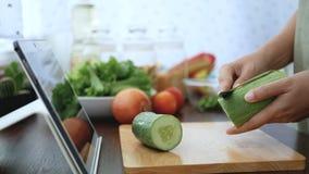 4K 妇女用途在片剂屏幕上的手指幻灯片和剥黄瓜,成份为烹调做准备跟随烹调网上录象剪辑 股票录像