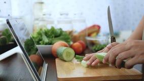 4K 妇女用途在片剂屏幕上的手指幻灯片和剥黄瓜,成份为烹调做准备跟随烹调网上录象剪辑 股票视频