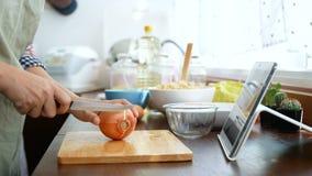 4K 妇女用途在片剂屏幕,切片上的手指幻灯片和剥葱,成份为烹调做准备跟随烹调网上录影 影视素材