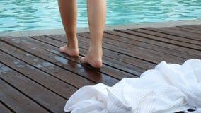 4K 妇女脱她的长袍走到游泳场在旅馆手段 在夏时的放松和休闲 股票视频