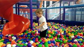 4k 3岁英尺长度使用与五颜六色的球的小孩男孩在水池操场 影视素材