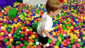 4k 3岁英尺长度使用与五颜六色的球的小孩男孩在水池操场 股票录像