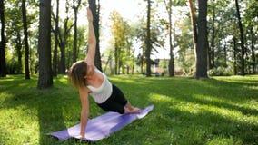 4k 40岁英尺长度做在席子的妇女健身锻炼在地方公园 人们照料他们精神和 影视素材
