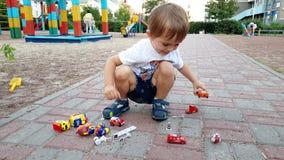 4k 3岁英尺长度坐地面在操场和使用与玩具汽车的小孩男孩 股票录像