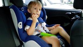 4k 3年英尺长度坐在儿童汽车安全位子和吃的小孩男孩 影视素材