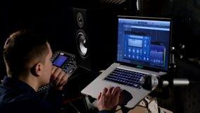 4K年轻录音师在使用膝上型计算机的录音室在混合的书桌 库存图片