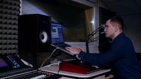 4K年轻录音师在使用膝上型计算机的录音室在混合的书桌 库存照片
