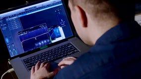 4K年轻录音师在使用膝上型计算机的录音室在混合的书桌 免版税库存照片
