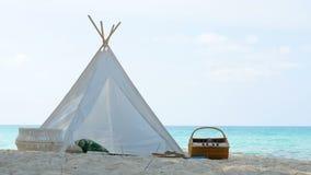 4K 浪漫白色野餐帐篷用在白色沙滩的篮子食物与透明的水和天空蔚蓝在背景 股票录像