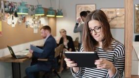 4K 特写镜头年轻可爱的深色的女实业家在现代起始的办公室使用触摸屏幕片剂 股票视频