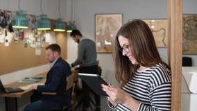 4K 特写镜头年轻可爱的深色的女实业家在现代起始的办公室使用触摸屏幕片剂 影视素材