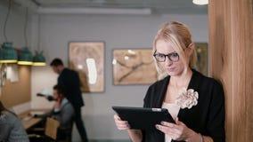 4K 特写镜头年轻美丽的白肤金发的女实业家在现代起始的办公室使用触摸屏幕片剂 股票视频