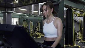 4K - 美丽的年轻女人运动员在结束锻炼会议的踏车走 股票视频