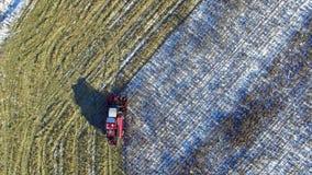 4K 联合收割机在麦地运转在第一雪以后!收割机切成熟干玉米 空中顶视图 股票录像