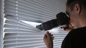 4K间谍、无固定职业的摄影师或者侦探射击在照相机通过窗帘 股票录像