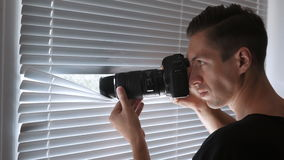 4K间谍、无固定职业的摄影师或者侦探射击在照相机通过窗帘 股票视频