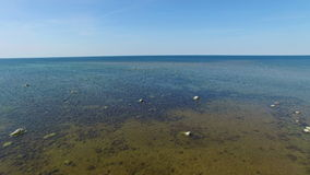 4K 飞行和起飞在海有站立在水中的石头的,鸟瞰图 股票视频