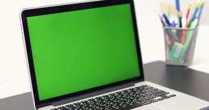 4K :有一个关键绿色屏幕集合的一台便携式计算机在工作办公室桌上 左到右移动式摄影车的移动 股票录像
