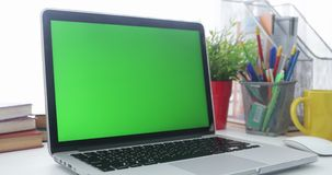4K :有一个关键绿色屏幕集合的一台便携式计算机在工作办公室桌上 移动式摄影车 影视素材