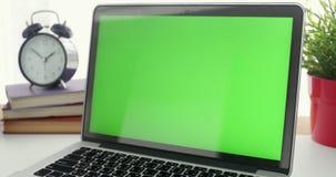 4K :有一个关键绿色屏幕集合的一台便携式计算机在工作办公室桌上 移动式摄影车 股票录像
