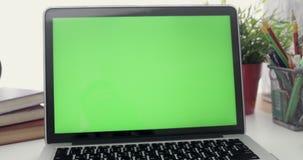 4K :有一个关键绿色屏幕集合的一台便携式计算机在工作办公室桌上 移动式摄影车 股票视频
