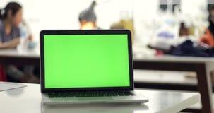 4K :有一个关键绿色屏幕集合的一台便携式计算机在工作办公室桌上 影视素材