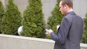 Молодой бизнесмен идя вниз по улице с беспроводными наушниками в ушах и пишет сообщение на телефоне сток-видео