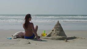 Ένα νέο κορίτσι σε ένα μαγιό κάθεται με την πίσω ενάντια σε ένα άσπρο σκυλί στην παραλία με ένα κάστρο άμμου 4K απόθεμα βίντεο