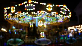 4K. abstract blur children`s merry-go-round carousel at night with bokeh light on festival for background.  stock video footage