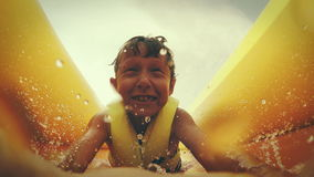 4K action footage: a kid slides down the waterside on his belly screaming from happiness.  stock footage