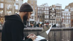 4K Adult 30s businessman uses laptop outdoors. Concentrated man working online. Mobile workplace. Amsterdam old town. 4K Adult 30s businessman uses laptop stock video footage