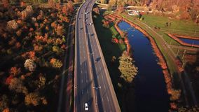 4K AERIAL: Cars and semi truck driving on busy highway across the country in beautiful autumn evening. People on road trip traveli. Ng on busy freeway at golden stock video
