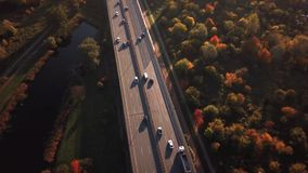 4K AERIAL: Cars and semi truck driving on busy highway across the country in beautiful autumn evening. People on road trip traveli. Ng on busy freeway at golden stock footage