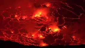 4k aerial close up shot of melting lava erupting at active Nyiragongo volcano crater lake in Congo Africa at night time