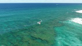4k aerial drone camera tropical seascape shot of professional windsurfer gliding in calm turquoise blue ocean wave water. Aerial drone camera tropical seascape stock video footage