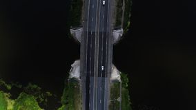 Cars drive on the highway located between the blue lake. 4k. Aerial drone footage. Cars drive on the highway located between the blue lake. The sky is reflected stock footage