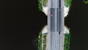 Cars drive on the highway located between the blue lake. 4k. Aerial drone footage. Cars drive on the highway located between the blue lake. The sky is reflected stock video footage