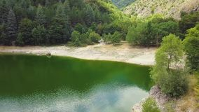 4k aerial drone footage of green mountain side with artificial lake by a dam stock video footage