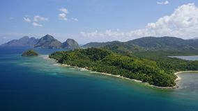 4K Aerial drone high attitude view flying towards a deserted tropical beach on mainland with towering limestone karst. Mountain ridge covered by jungle in stock video footage