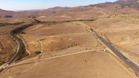 4k aerial drone panorama of huge modern urban passenger train moving through dry desert canyon in sand steppe landscape. Aerial drone panorama of huge modern stock video