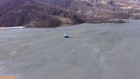 4k Aerial drone view,  ecological catastrophe, flooded church under mining waste water. Flying over chemical waste, water polluted with contaminated mining stock footage