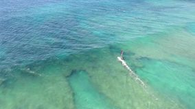 4k aerial drone view of professional windsurfer gliding in calm waves of turquoise blue ocean water Hawaiian seascape. Aerial drone view of professional stock footage
