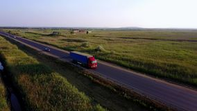 4K AERIAL: Flying high above container semi truck transporting goods on busy highway across the country in beautiful. Summer evening. Traffic driving and stock video footage
