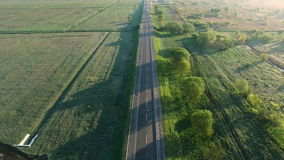 4K aerial footage of a car trucks buses riding on a road between green fields in the sun rise stock video