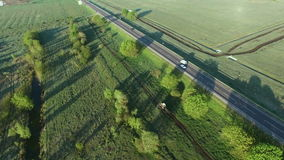 4K aerial footage of a tractor riding on a field road along asfalt road stock video