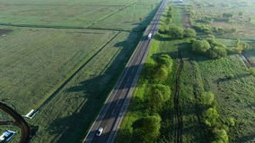 4K aerial footage of a truck riding on a road between green fields in the sun rise. 4K aerial white truck riding on a road between green fields in the sun rise stock video