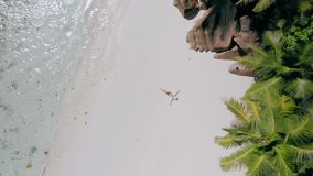 4k aerial move up footage from girl laying on a sandy beach surrounded by crystal clear turquoise shallow ocean lagoon. 4k aerial view vertical move up footage stock footage