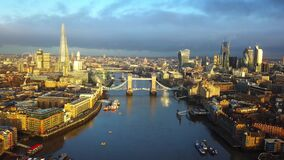 4K aerial skyline view of East London at sunrise with Tower Bridge and skyscrapers